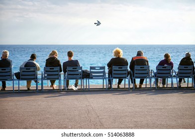 People relaxing on the beach, sitting down on comfortable sunbed and enjoy their time, fresh air and freedom, rear view, holidays travel concept. Flying bird in the sky.