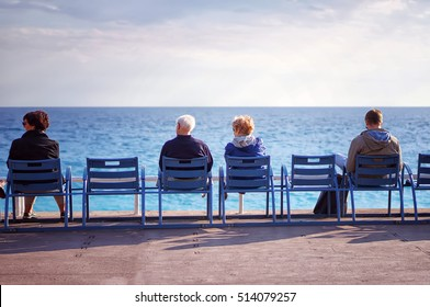 People relaxing on the beach, sitting down on comfortable sunbed and enjoy their time, fresh air and freedom, rear view, holidays travel concept.