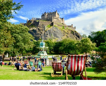 People relaxing in Princes street gardens, in front of Edinburgh Castle and the new Ross Fountain. Princes street, Edinburgh City, Scotland UK. August  2018