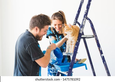 People, renovation and repair concept - portrait of happy couple with cat pour paint
