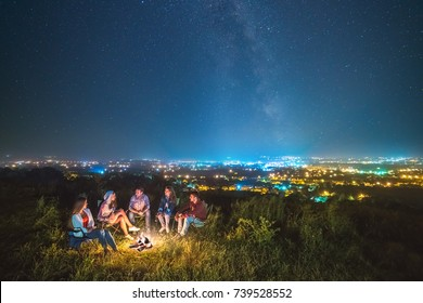 The people rest near a bonfire on the starry sky background. evening night time