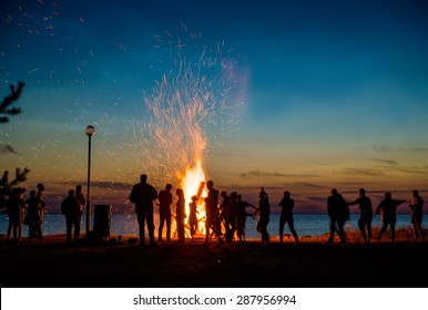 People resting near big bonfire outdoor at night
