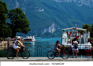people ride bicycles on the bridge across Annecy Lake, Annecy, France, July 30, 2015