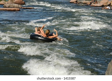 People ride an inner tube down the river rapids