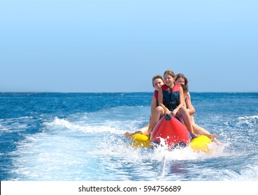 People ride on banana boat. Bright blue sea and clear sky. Happy vacations.