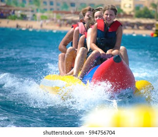 People ride on Banana boat on sunny summer day. Beach water sport