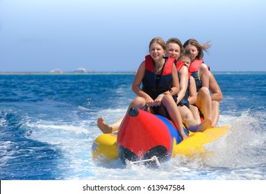 People ride on banana boat. Bright blue sea and clear sky. Happy vacation. Beach water sport