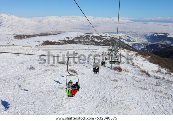 People ride on cableway at winter day in Cahkadzor resort in mountains; Hrazdan town far away