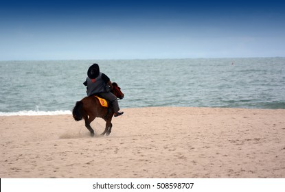 People riding on horse back at the thailand beach