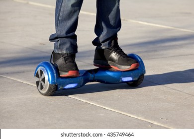 People riding on hoverboards or gyro scoter drive. Two wheel transport device. Electriic hyroscooter driving. Driving giroscooter. Hyroscooter.