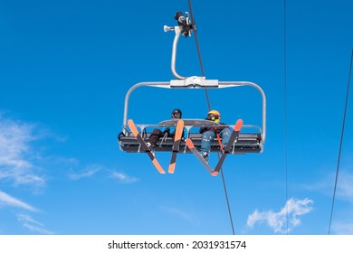 People riding ski chairlift. View from below. Group of people traveling on ski lift on top of mount for enjoing ski and snowboard. Winter sport, travel and vacation concept.