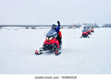 People riding snowmobiles and waving hands on the frozen lake in winter Rovaniemi in Lapland, Finland