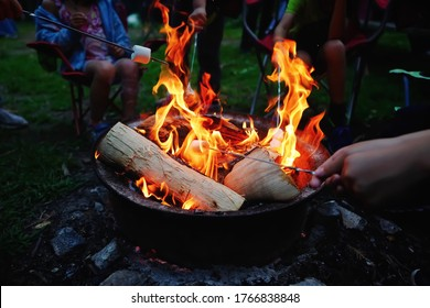 People roasting marshmallows on skewers on fire pit at campsite. Enjoying summer vacation outdoor camping fun and friend togetherness relaxing time when park and campsite reopen after covid lockdown.