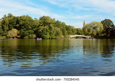 People rowing boats on The Lake in Central Park. Bow Bridge spans the water between green trees in early fall.