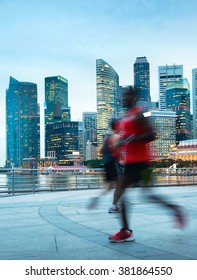 People running at dusk on Singapore embankment. Singapore Downtown Core in the background