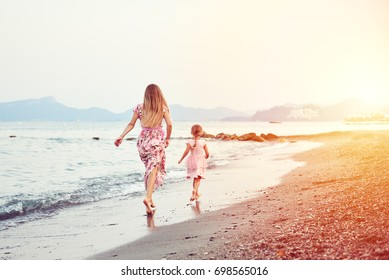 People running on the beach. Young woman and little girl wearing summer dresses having fun at the sea.