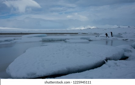 People running on broken glacier ice floes in winter Iceland