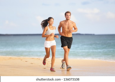 People running - young couple jogging on beach. Attractive fit sporty young couple runners side by side on the beach in the summer sunshine enjoying the fresh air as they train together