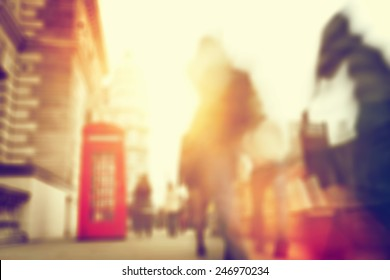 People rush on a busy street of London. Blur, defocused. Sun shining.