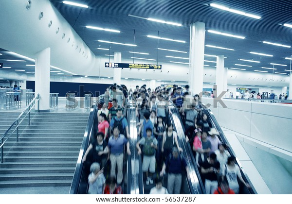 People rush on a escalator motion blurred