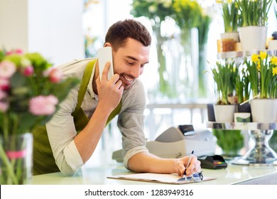 people, sale, retail, business and floristry concept - happy smiling florist man calling on smartphone and making notes to clipboard at flower shop counter