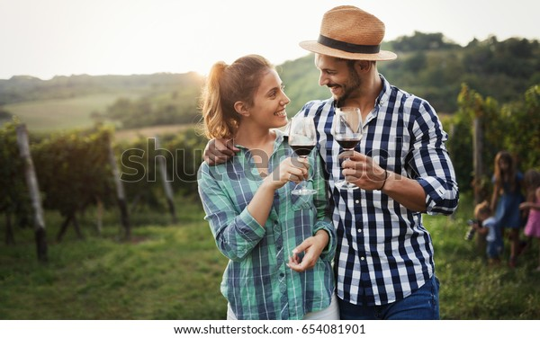 People sampling and tasting wines in vineyard