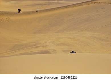 People sandboarding on the ancient dunes of the Namib Desert, Namibia, Africa.
