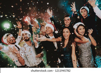 People in Santa Claus Cap Celebrating New Year. Happy New Year. People Have Fun. Indoor Party. Celebrating of New Year. Young Woman in Dress. Young Man in Suit. Happy People. Red Cap.
