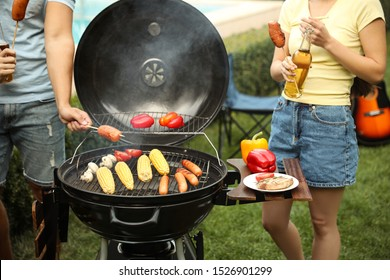 People with sausages near barbecue grill outdoors, closeup