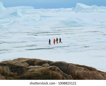 :People, scientists, researchers are on the mountain of stone. Near the shore of the ocean and icebergs. Antarctic.