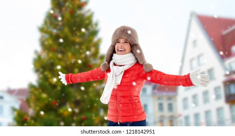 people, season and leisure concept - happy woman in winter fur hat over christmas tree at tallinn old town hall square background and snow