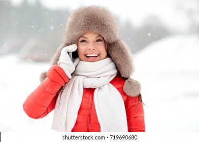 people, season and leisure concept - happy smiling woman in winter fur hat calling on smartphone outdoors