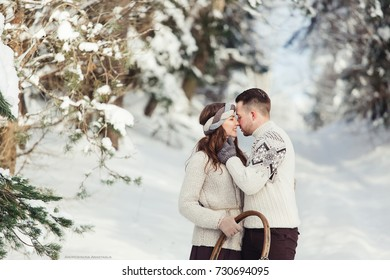 People, season, love and leisure concept - happy couple hugging and laughing outdoors in winter. Couple embracing in snowy winter park