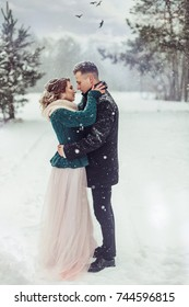 People, season, love and leisure concept - happy couple hugging and laughing outdoors in winter. Couple embracing in snowy winter park.Winter wedding of stylish beautiful young couple bride and groom