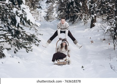 People, season, love and leisure concept - happy couple hugging and laughing outdoors in winter. Couple embracing in snowy winter park and riding a sled