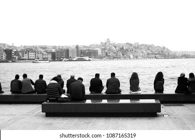 people seating on the pier near the sea