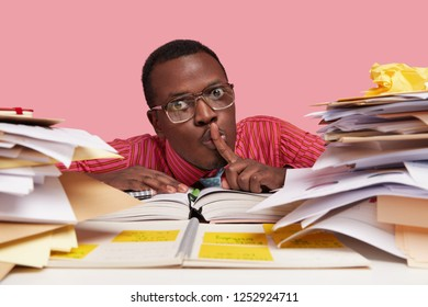 People, secrecy and education concept. Close up portrait of dark skinned clever student keeps index finger over mouth, shows shush gesture, wears spectacles, surrounded with notepad and papers
