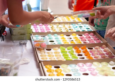 people selecting colorful thai sweet in market