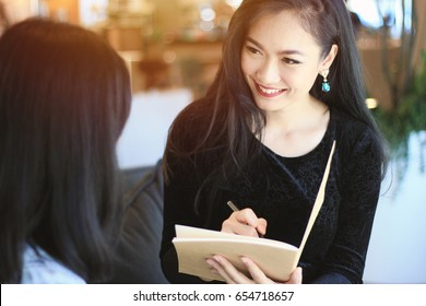 People and service concept, young asian smart businesswoman filling the information on paperwork for customer