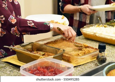 People serving themselves Thanksgiving dinner from various different casseroles and pans