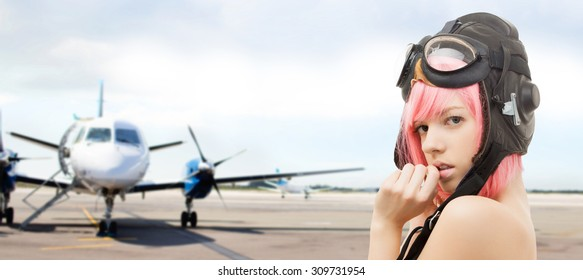 people, sexuality, aviation and role-playing games concept - pink hair girl in aviator helmet over plane in airport background