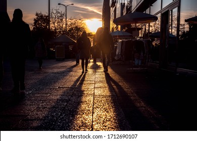 People and its shadows walking in the street during the sunset. Agglomeration.