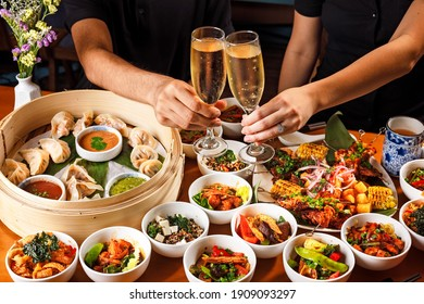 People sharing a drink and a large Asian meal