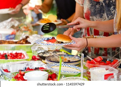 People sharing food at a summer potluck barbeque