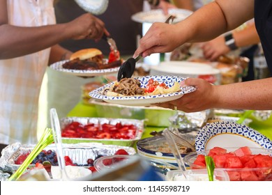People sharing food at a summer potluck event