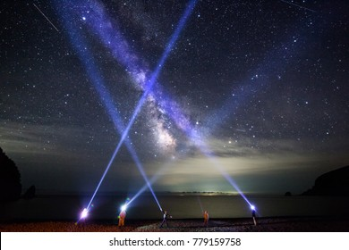 People shine with led flashlights to night sly with milky way