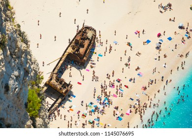 people and ship wreck on Navagio beach, Zakynthos, Greece, in the foreground of rock