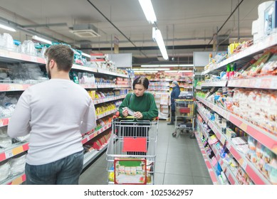 People shop at a supermarket. A girl walks through a supermarket, a man chooses goods from shelves. Shopping in a supermarket concept