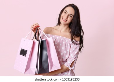 People and shopping concept. Happy dark haired woman shopaholic dressed in polka dot dress, carries shopping bags, isolated over pink background, has red manicure. Female customer stands indoor