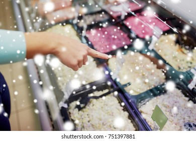 people, shopping, sale and food concept - customer hand pointing at salads on grocery stall over snow